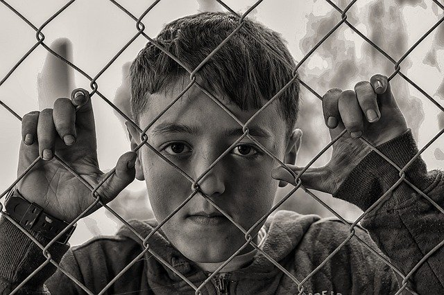 boy behind wire fence